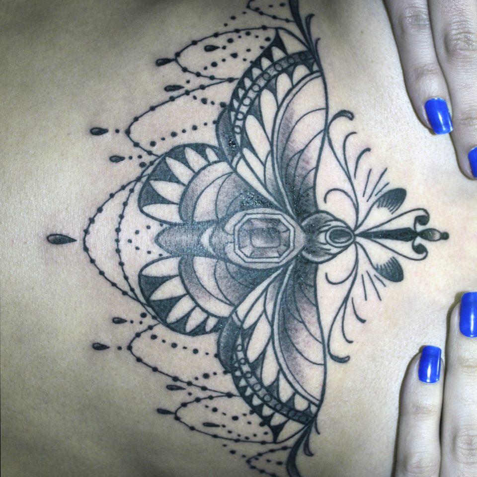 Tattoo bajo pecho mariposa tradicional
